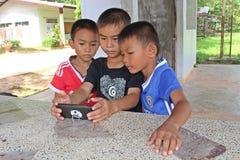 Tre pojkar håller ögonen på intresset på en telefon Royaltyfri Bild