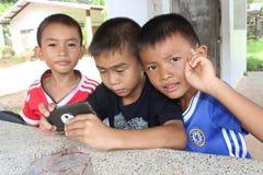 Tre pojkar håller ögonen på intresset på en telefon Arkivbild