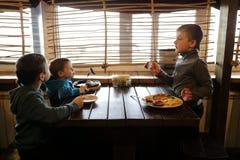 Tre pojkar har lunch royaltyfri foto