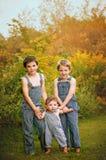 Tre pojkar som står höstståenden Arkivbild