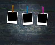 Tre Polaroids in bianco che appendono su una riga di vestiti Immagine Stock