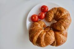 Tre pomodori e croissant rossi Fotografie Stock