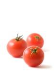 Tre pomodori su bianco Immagine Stock