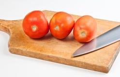 Tre pomodori su una tavola Fotografia Stock