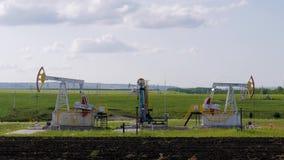 Tre pompe di olio funzionanti sulla terra fra i campi verdi archivi video