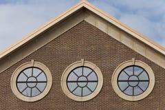 Tre portalstilfönster på tegelstenväggen med molnig blå himmel Royaltyfri Fotografi