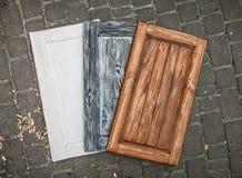 Tre porte di legno colorate che si trovano sulla pavimentazione della strada Fotografie Stock