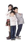 Tre poserade lyckliga gulliga barn Royaltyfria Foton