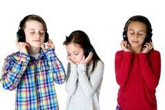 Tre preteens som lyssnar till musik med hörlurarögon, stängde sig Arkivbilder