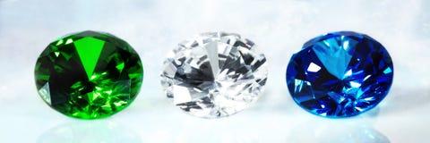 Tre prickfria briljanta klippta juvlar, safir, smaragd och diamant royaltyfri foto