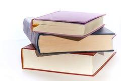 Tre primi piani dei libri dei colori differenti si trovano sopra a vicenda Bianco del fondo immagini stock libere da diritti