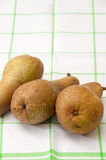Tre päron på en maträtthandduk Arkivfoton