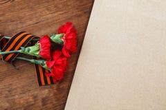 Tre röd blomma och papper på en träbakgrund Bild för selektiv fokus Arkivfoton