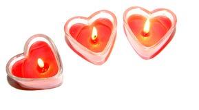 Tre röd hjärta formade stearinljus Fotografering för Bildbyråer