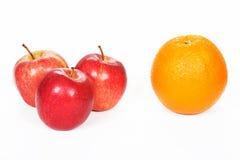 Tre röda äpplen och apelsin Royaltyfri Foto