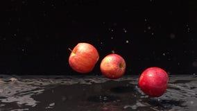 Tre röda äpplen som ner faller till det mörka golvet lager videofilmer