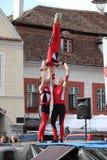 Tre röda akrobater på en trampolin Arkivfoton