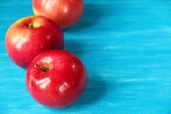 Tre röda Apple på en blå tabell Fotografering för Bildbyråer