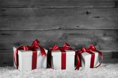 Tre röda gåvor för vit jul på gammal trägrå bakgrund royaltyfria foton