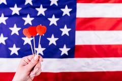 Tre röda hjärtor formar på pinnen framme av amerikanska flaggan Visuellt begrepp av förberedelsen för självständighetsdagen Fjärd Royaltyfria Foton