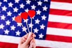 Tre röda hjärtor formar på pinnen framme av amerikanska flaggan Visuellt begrepp av förberedelsen för självständighetsdagen Fjärd Arkivfoton