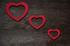 Tre röda hjärtor som diagonalt ordnas på ett gammalt träbrunt valentin dagbräde royaltyfria foton