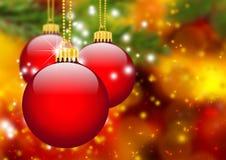 Tre röda julbollar som framme hänger av abstrakt granträd Royaltyfria Foton