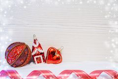 Tre röda julleksaker och det röda vridna bandet ligger på snö på ljus träbakgrund Fotografering för Bildbyråer