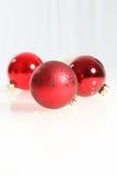 Tre röda julstruntsaker Arkivfoto