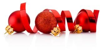 Tre röda julstruntsaker och krullande papper som isoleras på vit Royaltyfria Bilder