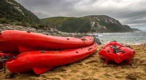 Tre röda kanoter på stranden royaltyfria bilder