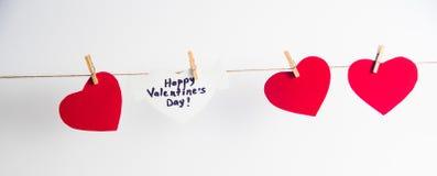 Tre röda pappers- hjärtor och en vit hjärta med lyckönskan och vingar fixade med klädnypor på en kabel vitt Royaltyfri Foto