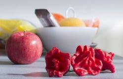 Tre röda peppar och ett äpple royaltyfri bild