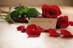 Tre röda rosor med kronblad på den wood tabellen och det pappers- kortet för valentindag Royaltyfri Fotografi