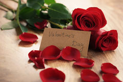 Tre röda rosor med kronblad på den wood tabellen och det pappers- kortet för valentindag Royaltyfria Foton