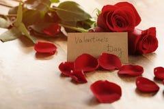 Tre röda rosor med kronblad på den wood tabellen och det pappers- kortet för valentindag Arkivbilder