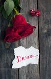 Tre röda rosor på den lantliga tabellen med handskrivet ord drömmer Royaltyfria Bilder