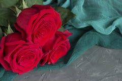 Tre röda rosor på grå färgbetongbakgrund fotografering för bildbyråer