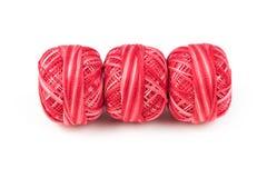 Tre röda sömnadtrådar i rad på en vit bakgrund Royaltyfria Foton