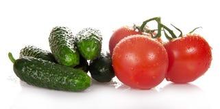 Tre röda tomater och hög av gurkorna, royaltyfria bilder