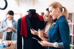 Tre ragazze alla fabbrica dell'indumento con il nuovo vestito Uno di loro sta tenendo le forbici immagine stock libera da diritti