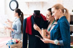 Tre ragazze alla fabbrica dell'indumento con il nuovo vestito Uno di loro sta tenendo le forbici fotografia stock libera da diritti