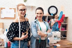 Tre ragazze alla fabbrica dell'indumento Due di loro che tengono i paii di forbici immagini stock