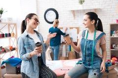 Tre ragazze alla fabbrica dell'indumento Due di loro stanno bevendo il caffè che parlano e che sorridono fotografia stock libera da diritti