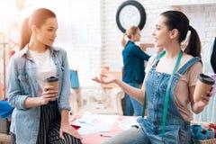 Tre ragazze alla fabbrica dell'indumento Due di loro stanno bevendo il caffè che parlano e che sorridono fotografia stock
