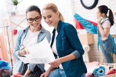 Tre ragazze alla fabbrica dell'indumento Due di loro stanno esaminando le nuovi progettazioni e sorridere fotografia stock libera da diritti