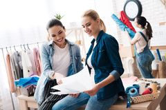 Tre ragazze alla fabbrica dell'indumento Due di loro stanno esaminando le nuovi progettazioni e sorridere immagini stock libere da diritti