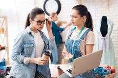 Tre ragazze alla fabbrica dell'indumento Stanno cercando desing per il nuovo vestito sul computer portatile fotografia stock