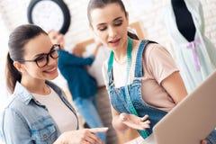 Tre ragazze alla fabbrica dell'indumento Stanno cercando desing per il nuovo vestito sul computer portatile immagini stock