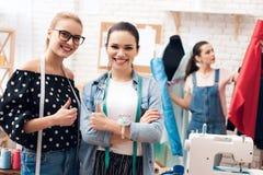 Tre ragazze alla fabbrica dell'indumento Stanno dando i pollici su hanno finito il nuovo vestito fotografia stock